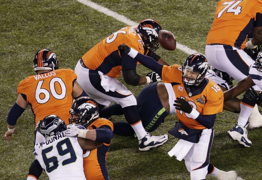 Quarterback Peyton Manning #18 of the Broncos has a pass blocked. Photo: Win McNamee, Getty Images