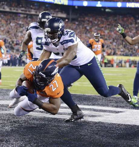 Seattle's Cliff Avril (56) tackles Denver's Knowshon Moreno in the end zone for a safety after a bad snap on the game's first play from scrimmage. Photo: Lionel Hahn, MBR / Abaca Press