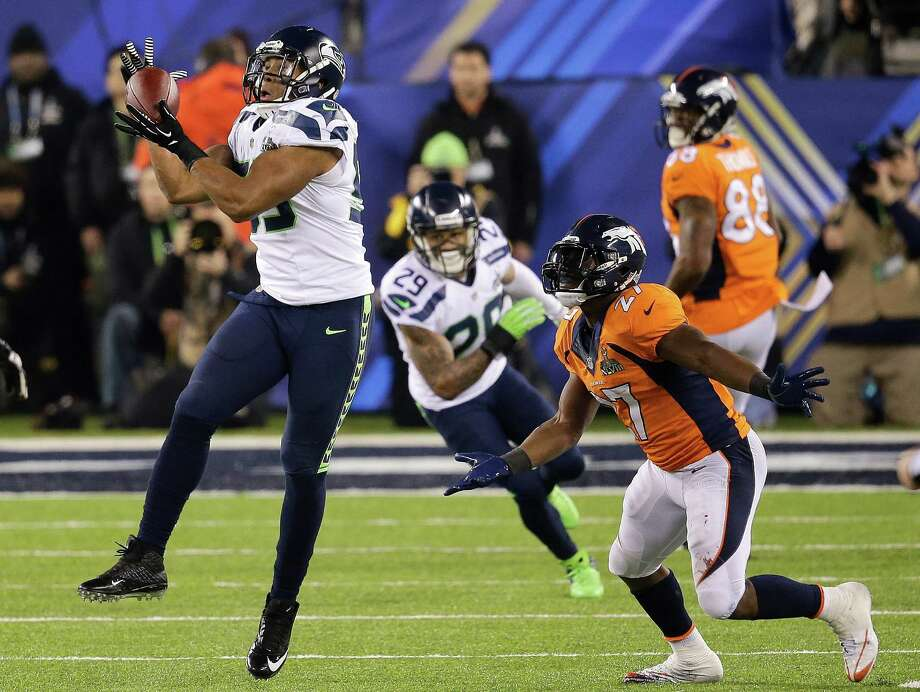Seahawks linebacker Malcolm Smith, left, intercepts a pass in front of Broncos running back Knowshon Moreno before returning it 69 yards for a pivotal touchdown and a 22-0 lead in the first half Sunday. Photo: Chris O'Meara, STF / AP