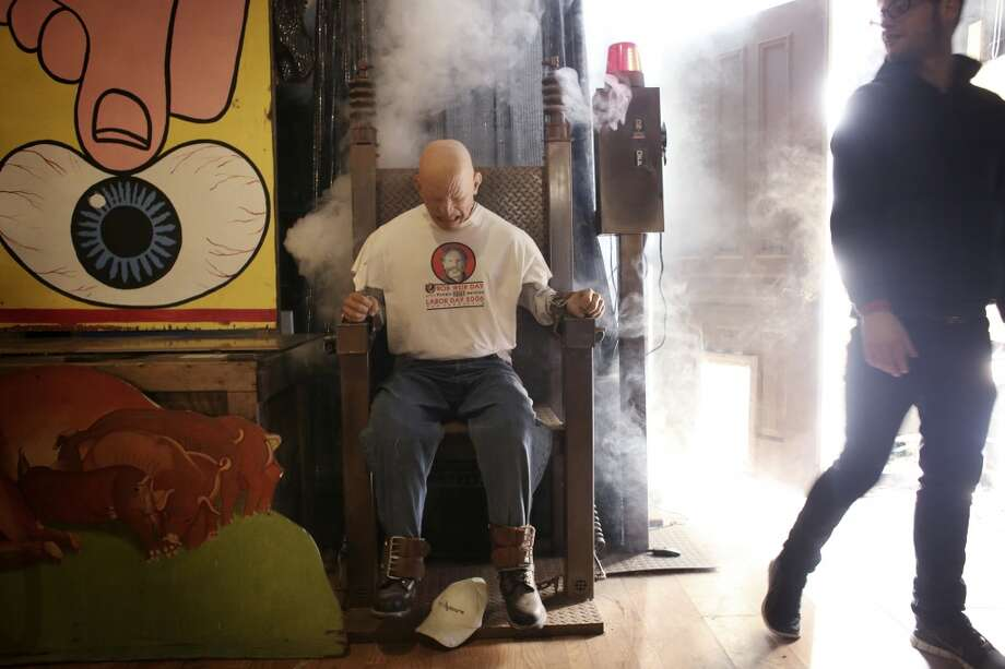 Bob Pritikin's assistant  Chris Johnson stands back after turning on the dummy in an electrocution chair in a downstairs room of The Pritikin Museum in San Francisco, Calif. Photo: The Chronicle