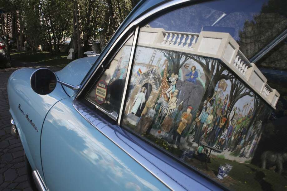 Reflections of a mural of more than 50 famous and infamous people of San Francisco past and present shine in Kaiser car outside The Pritikin Museum in San Francisco, Calif. Photo: The Chronicle
