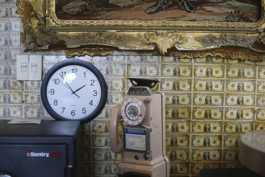 Dollar bills and a framed tapestry of George Washington cover the inside corner of The Pritikin Museum in San Francisco, Calif. Photo: The Chronicle