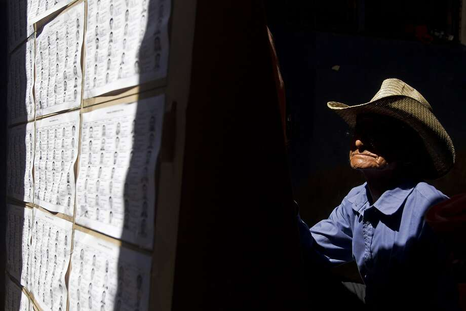 A man scans the electoral rolls in search of his polling table location during the presidential election, in Panchimalco, on the outskirts of San Salvador, El Salvador, Sunday, Feb. 2, 2014. Presidential elections in two Central American countries Sunday are both referendums on political stagnation, with voters in Costa Rica deciding whether to oust the long-ruling party, and voters in El Salvador deciding whether to bring it back to power.  (AP Photo/Esteban Felix) Photo: Esteban Felix, Associated Press