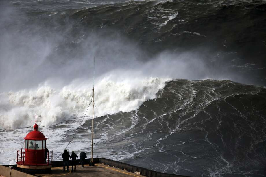 People watch huge waves approaching towards Nazare lighthouse, outside the fishing village of Nazare, in the central coast of Portugal, Sunday, Feb. 2, 2014. According to the Portuguese weather institute waves above six metres high were expected to hit the coastline and few ports, most of them in the north of the country, were closed due to the rough sea. (AP Photo/Francisco Seco) Photo: Francisco Seco, Associated Press
