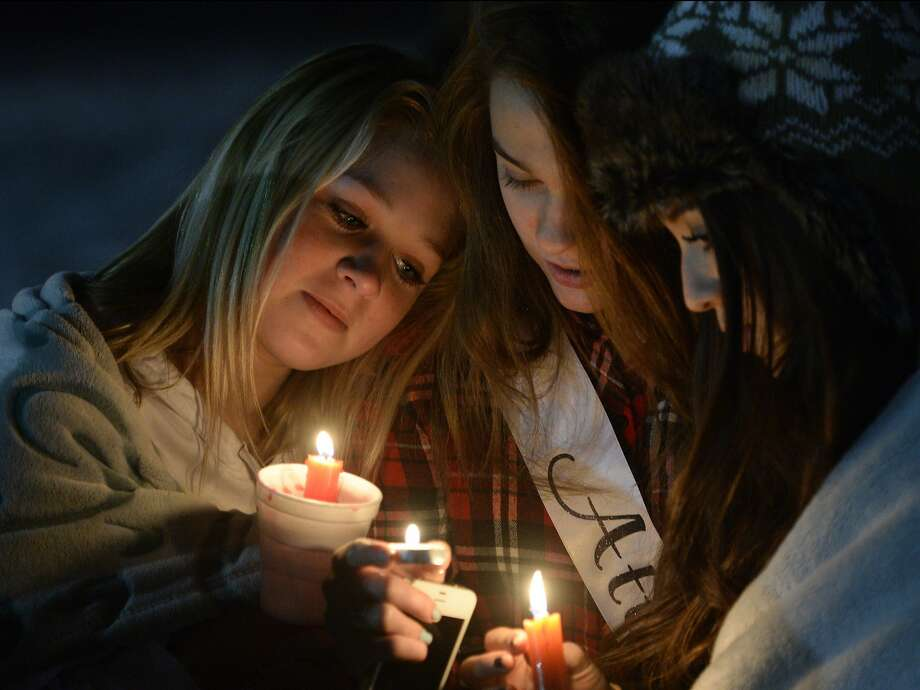 Cheyenne Davis, Tamsen Argyle, and Leilany Montoya, hold candles at the candlelight vigil in honor of Sgt. Cory Wride and injured Deputy Greg Sherwood, in Spanish Fork, Sunday, Feb. 2, 2014. (AP Photo/The Salt Lake Tribune, Rick Egan) Photo: Rick Egan, Associated Press