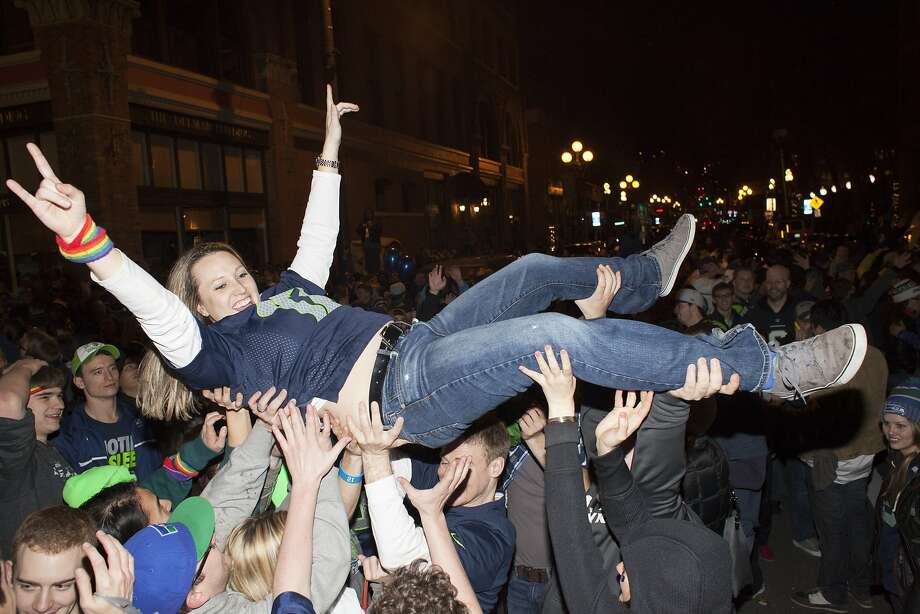 SEATTLE, WA - FEBRUARY 2: Seattle Seahawks fan Sara Hatfielf surfs through the crowd in the middle of 1st Avenue on February 2, 2014 in Seattle, Washington. Hundreds of people flooded the streets of downtown Seatle after the Seahawks defeated the Denver Broncos in the Super Bowl.  (Photo by David Ryder/Getty Images) Photo: David Ryder, Getty Images