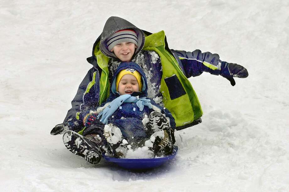 Trenton Mercer, and his brother, Chase, 2, sled down a hill at Riverview Elementary School, Sunday, Feb. 2, 2014, in Marion, Ind. (AP Photo/The Chronicle-Tribune, Jeff Morehead) Photo: Jeff Morehead, Associated Press