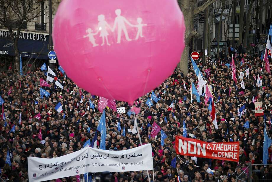 "People wave trademark pink, blue and white flags during a protest march called, ""La Manif pour Tous"" (Demonstration for All) against France's legalisation of same-sex marriage and to show their support of traditional family and education values, in Paris February 2, 2014. In April 2013 the French parliament approved a law allowing same-sex couples to marry and to adopt children, a flagship reform pledge by the French president. Banners read, ""French Muslims Say NO to Mariage of Homosexuals"" (L) and ""No to Gender Theory"" (R).          REUTERS/Benoit Tessier (FRANCE  - Tags: POLITICS TPX IMAGES OF THE DAY) Photo: Benoit Tessier, Reuters"