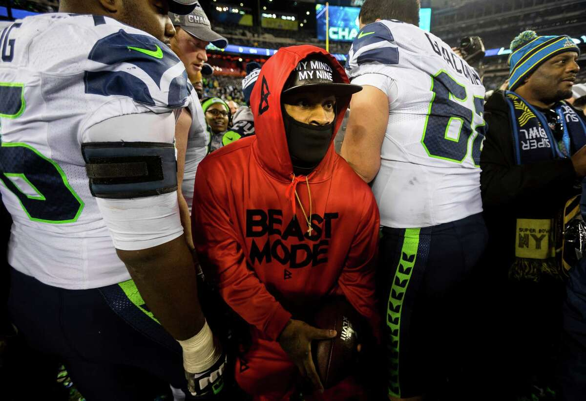 A masked Marshawn Lynch sneaks through a pack of Seahawks teammates while attempting to evade a media onslaught following Super Bowl XLVIII Sunday, Feb. 2, 2014, at MetLife Stadium in New Jersey. The Seahawks beat the Broncos 43 - 8 to clinch the championship.