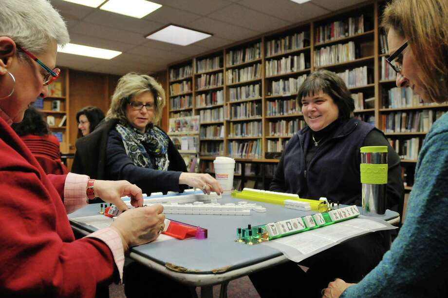 Carol Bloom, left, from Delmar, Sandra Gollop, second from left, from Delmar, Amie Bloom, third from left, from Selkirk and the daughter of Carol, and Lisa Roth, right, from Slingerlands, take part in a game of Mahjong at Congregation Beth Emeth on Sunday, Feb. 2, 2014 in Albany, NY.  The four women have enjoyed their time together so much that they plan on gathering in the evenings to keep playing the game with each other.    This is the second year that the congregation has held the Mahjong sessions over the winter months.  The sessions are set up in groups of two consecutive Sundays where the first Sunday participants learn the game and then the next Sunday they meet up again to play the game.  Next Sunday will be the final day for this winter but Congregation Beth Emeth will be holding the Mahjong lessons/games again next winter.  (Paul Buckowski / Times Union) Photo: Paul Buckowski / 00025328A
