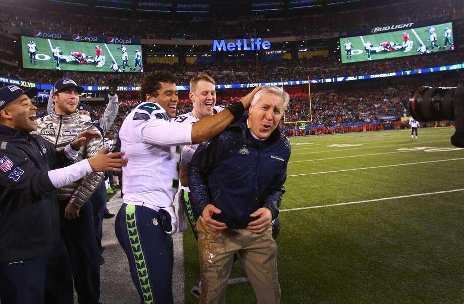 Russell Wilson celebrates with Pete Carroll after Gatorade was duped on the coach in the final minutes of the Super Bowl on Sunday, February 2, 2014 at MetLife Stadium in New Jersey. The Seahawks dominated the Denver Broncos 42-8. (Joshua Trujillo, seattlepi.com) Photo: SEATTLEPI.COM