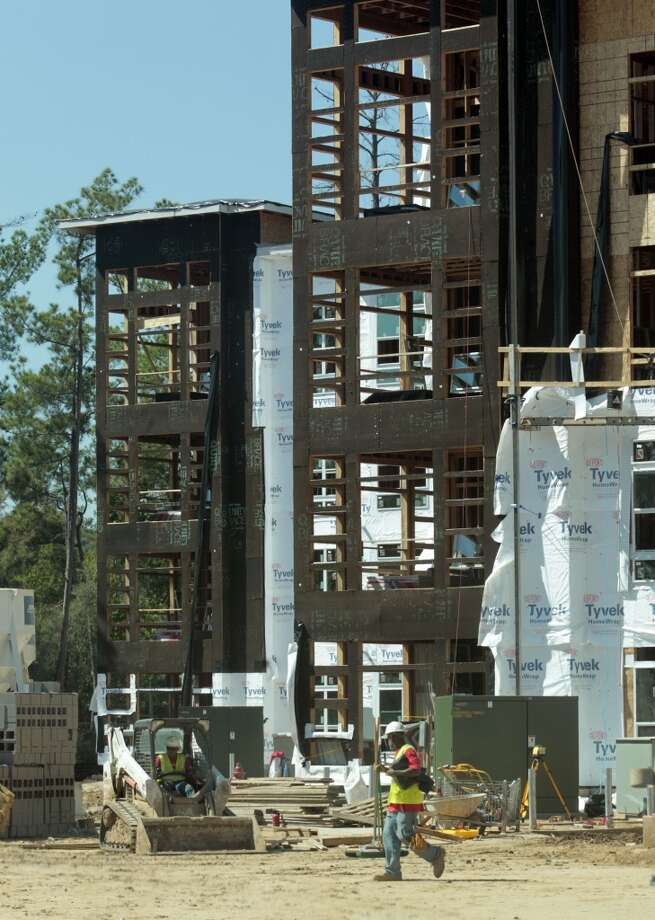 Workers construct multi-family units  Wednesday October 9, 2013 in the Springwoods Village master-planned community adjacent to the Exxon Mobil campus, in Spring, Texas. (Billy Smith/Chronicle) Photo: Billy Smith II, Houston Chronicle