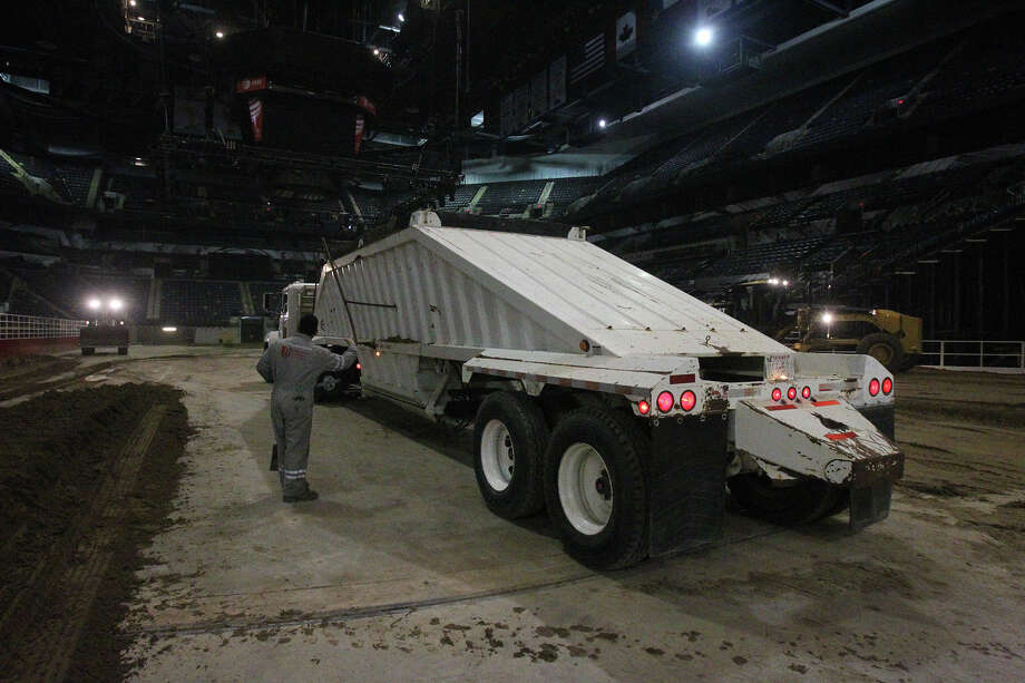 Miguel Ramirez, (right) an employee of Unison Drilling, guides a truck full of dirt Monday February 3, 2014 on the floor of the AT&T Center. The AT&T Center is undergoing the traditional conversion from the home of the Spurs to the home of the San Antonio Stock Show & Rodeo. The arena requires 2,160 tons of soil and takes 70 truckloads to move the soil from its storage location to the AT&T Center. Photo: JOHN DAVENPORT, SAN ANTONIO EXPRESS-NEWS / ©San Antonio Express-News/Photo may be sold to the public