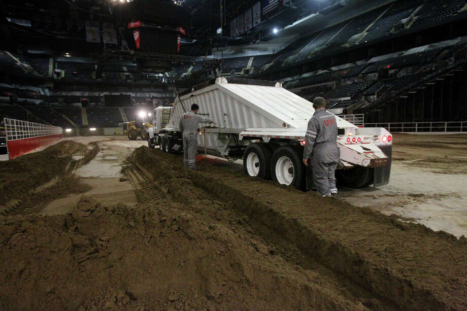 Employees of Unison Drilling guide a truck full of dirt Monday February 3, 2014 on the floor of the AT&T Center. The AT&T Center is undergoing the traditional conversion from the home of the Spurs to the home of the San Antonio Stock Show & Rodeo. The arena requires 2,160 tons of soil and takes 70 truckloads to move the soil from its storage location to the AT&T Center. Photo: JOHN DAVENPORT, SAN ANTONIO EXPRESS-NEWS / ©San Antonio Express-News/Photo may be sold to the public
