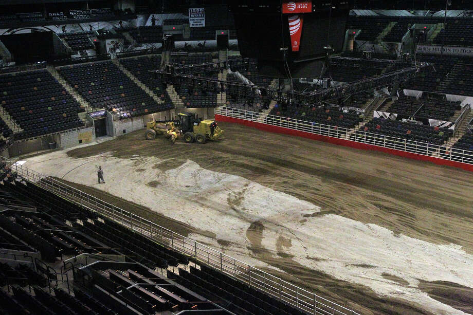 Miguel Ramirez, (left) an employee of Unison Drilling, watches Monday February 3, 2014 as dirt is spread on the floor of the AT&T Center. The AT&T Center is undergoing the traditional conversion from the home of the Spurs to the home of the San Antonio Stock Show & Rodeo. The arena requires 2,160 tons of soil and takes 70 truckloads to move the soil from its storage location to the AT&T Center. Photo: JOHN DAVENPORT, SAN ANTONIO EXPRESS-NEWS / ©San Antonio Express-News/Photo may be sold to the public