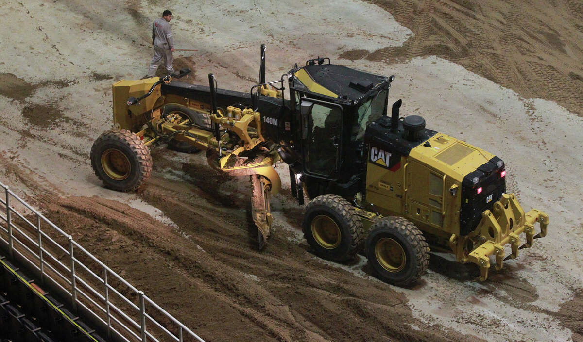 Miguel Ramirez, (left) an employee of Unison Drilling, watches Monday, Feb. 3, 2014, as dirt is spread on the floor of the AT&T Center. The AT&T Center is undergoing the traditional conversion from the home of the Spurs to the home of the San Antonio Stock Show & Rodeo. The arena requires 2,160 tons of soil and takes 70 truckloads to move the soil from its storage location to the AT&T Center.