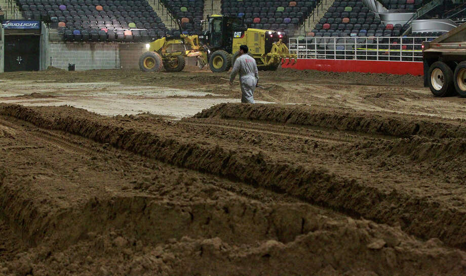 Miguel Ramirez, (center) an employee of Unison Drilling, watches Monday February 3, 2014 as dirt is spread on the floor of the AT&T Center. The AT&T Center is undergoing the traditional conversion from the home of the Spurs to the home of the San Antonio Stock Show & Rodeo. The arena requires 2,160 tons of soil and takes 70 truckloads to move the soil from its storage location to the AT&T Center. Photo: JOHN DAVENPORT, SAN ANTONIO EXPRESS-NEWS / ©San Antonio Express-News/Photo may be sold to the public