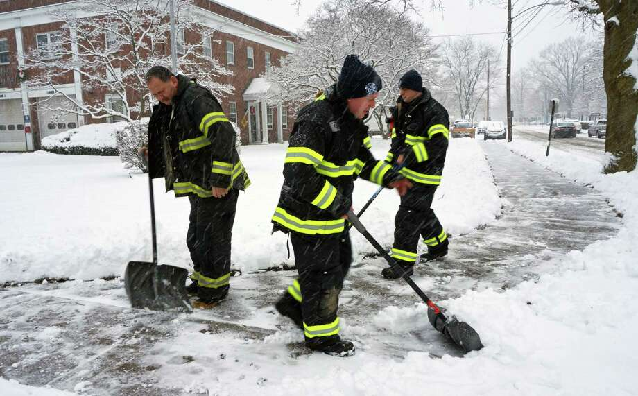 Firefighters clear snow in front of Fire Department headquarters on Reef Road Monday morning. Photo: Genevieve Reilly / Fairfield Citizen
