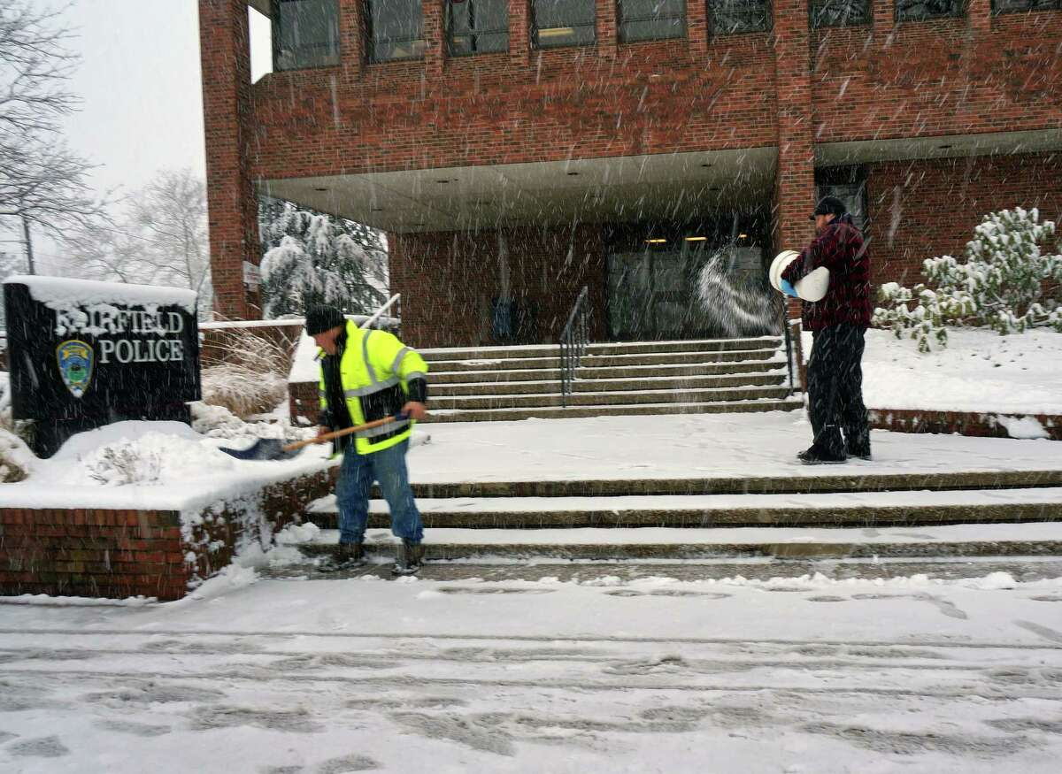 A Public Works crew clears away snow in front of police headquarters Monday.