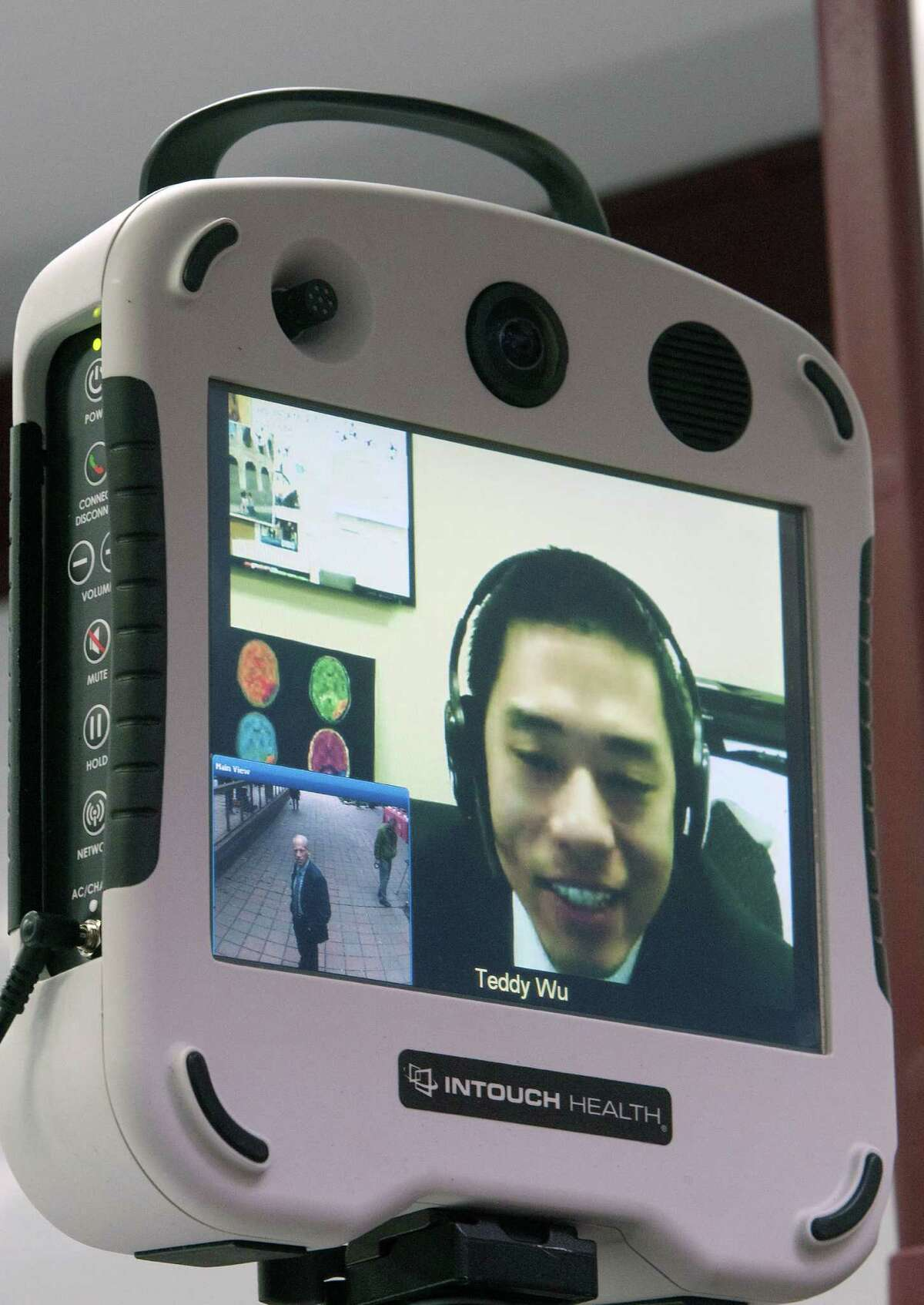 Dr. Tzu-Ching Wu, Director of Telemedicine, right, appears on a screen as M.D., director of stroke research in the Center for Innovation & Research at Memorial Hermann-TMC, James C. Grotta, left, stands outside the nation's first Mobile Stroke Unit to show the camera's ability at the University Of Texas Health And Science, Monday, Feb. 3, 2014, in Houston. On board the ambulance is a computed tomography (CT) scanner that allows a mobile stroke unit team member to quickly assess whether a patient is having a stroke caused by a blood clot and if so, the clot-buster tPA (tissue plasminogen activator) can be administered. Wu will be able to see what takes place in the ambulance via a camera as the stroke unit will be run in conjunction with the Emergency Medical Services of the Houston Fire Department, Bellaire Fire Department and West University Fire Department.