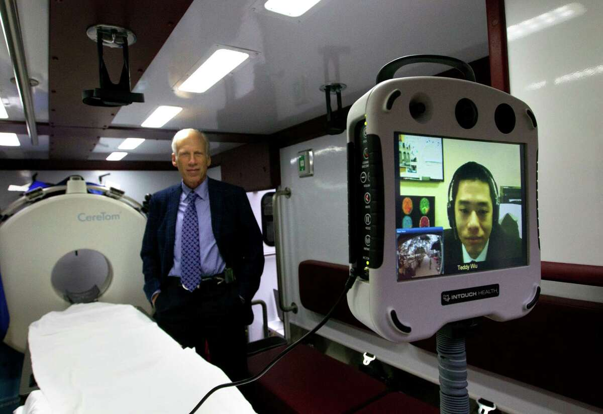 Dr. Tzu-Ching Wu, Director of Telemedicine, right, appears on a screen as M.D., director of stroke research in the Center for Innovation & Research at Memorial Hermann-TMC, James C. Grotta, left, stands inside the nation's first Mobile Stroke Unit at the University Of Texas Health And Science, Monday, Feb. 3, 2014, in Houston. On board the ambulance is a computed tomography (CT) scanner that allows a mobile stroke unit team member to quickly assess whether a patient is having a stroke caused by a blood clot and if so, the clot-buster tPA (tissue plasminogen activator) can be administered. Wu will be able to see what takes place in the ambulance via a camera as the stroke unit will be run in conjunction with the Emergency Medical Services of the Houston Fire Department, Bellaire Fire Department and West University Fire Department.