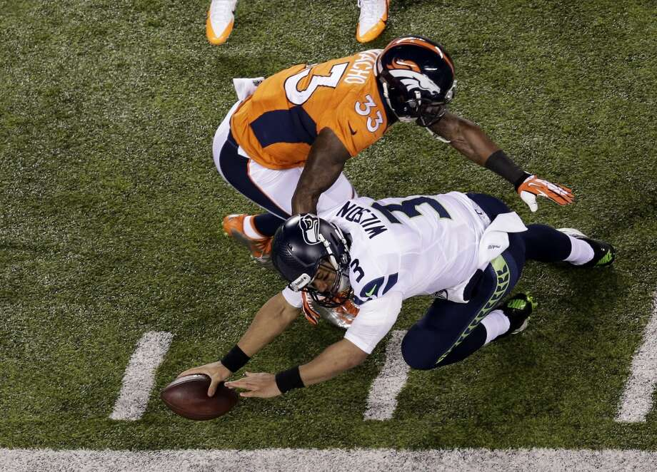 Quarterback Russell Wilson #3 of the Seattle Seahawks dives out of bounds with ball during the first quarter of Super Bowl XLVIII against Denver Broncos at MetLife Stadium on February 2, 2014 in East Rutherford, New Jersey.  (Photo by Win McNamee/Getty Images) Photo: Win McNamee, Getty Images