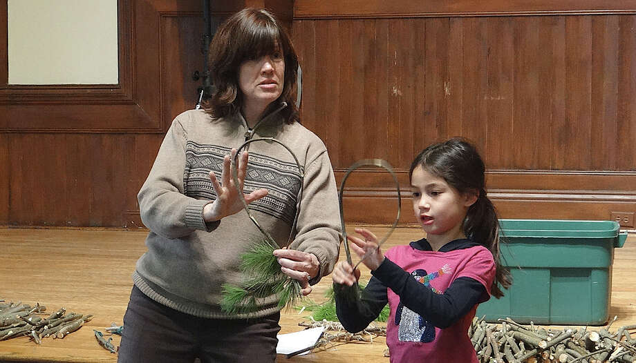 Connecticut Audubon Society naturalist Colleen Noyes shows Leilani Fleming, 7, how to carefully bend pine branches in a snowshoe-making workshop at Pequot Library last Friday. Photo: Mike Lauterborn / Fairfield Citizen contributed