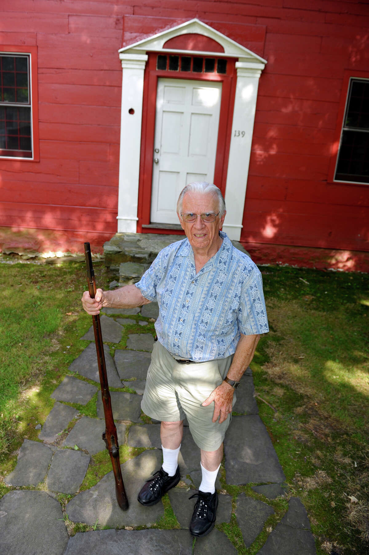 Milford historian Richard Platt with a Revolutionary War musket in front of the historic John Downs house in Milford, Conn. on July 3, 2012. The musket belonged to a British soldier who was killed in a battle and was taken by a relative of Platt's.