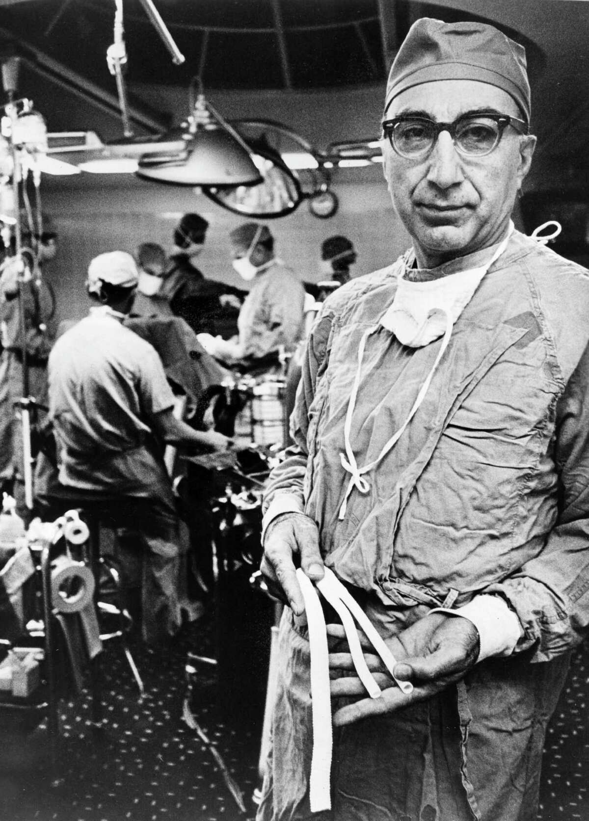 The gift of graft Baylor College of Medicine is credited with inventing the Dacron graft, which usually replaces or repairs blood vessels. Houston's Dr. Michael Ellis DeBakey was the first U.S. surgeon to remove an aneurysm in the aorta near the stomach.Here, Dr. DeBakey holds arterial grafts in 1966, fabricated from knitted Dacron tubing which have proven to be, in this gifted surgeon's hands, a lifesaving device for hundreds of his patients.