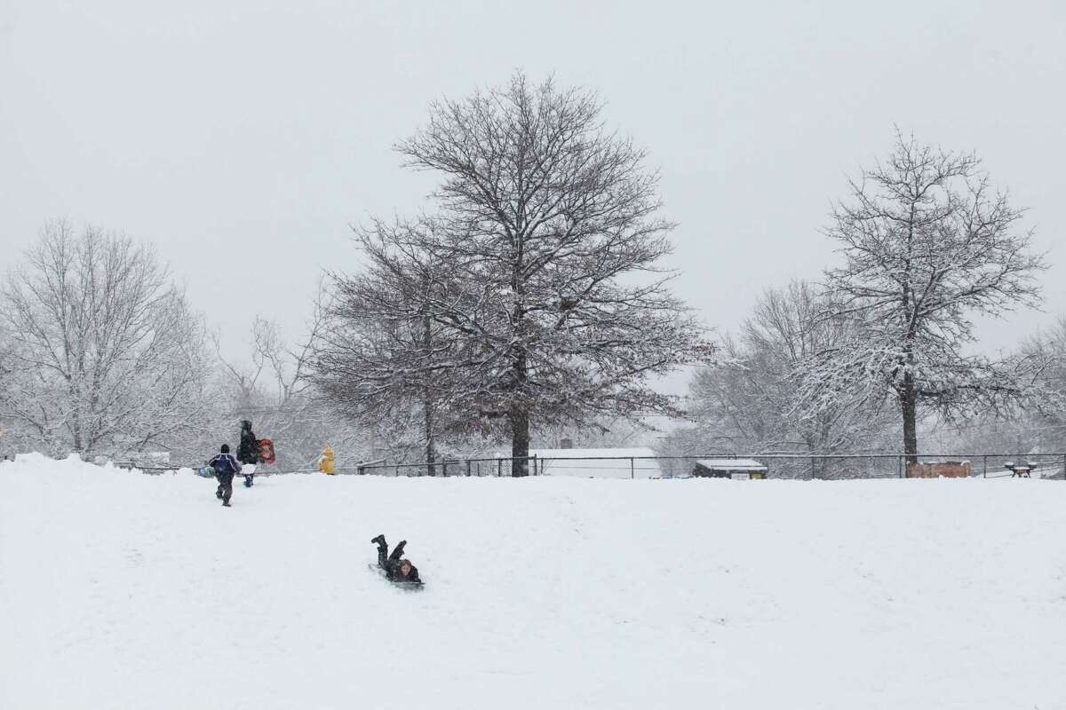 A few children have the hill to themselves during the afternoon at Jonathan Law High School in Milford, Conn. on Monday, Feb. 3, 2014.