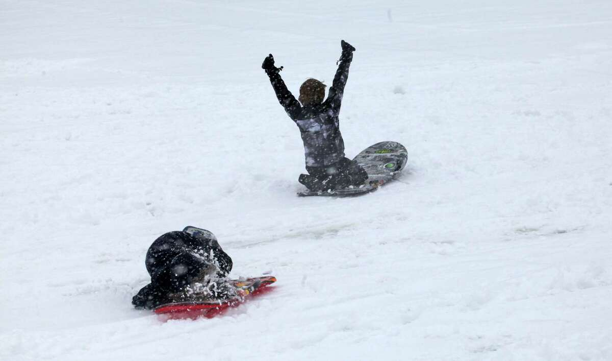 Riley Wargo, 9, celebrates after beating Jane Iwanicki, 11, down a hill at Jonathan Law High School in Milford, Conn. on Monday, Feb. 3, 2014.