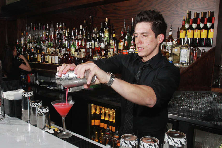 Bartender Mike Gonzalez making a French Martini at Marfreless, the River Oaks bar which has reopened after extensive renovations. It celebrated its 40th anniversary just months before closing in February of 2013. Photo: Gary Fountain, For The Houston Chronicle / Copyright 2014 Gary Fountain.