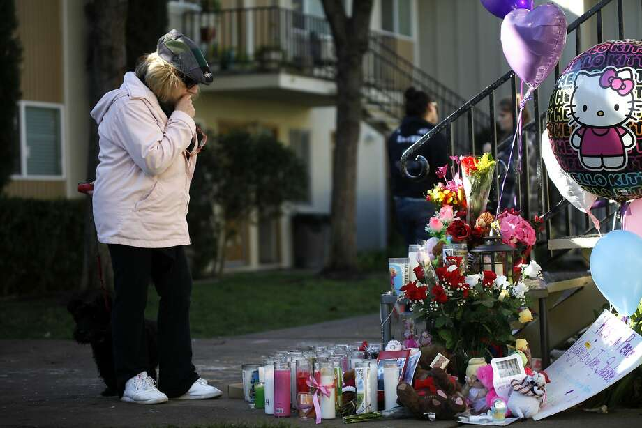Roisin Ariaz prays at a makeshift memorial outside the building where 3-year-old Kayleigh Slusher died. Photo: Lacy Atkins, The Chronicle