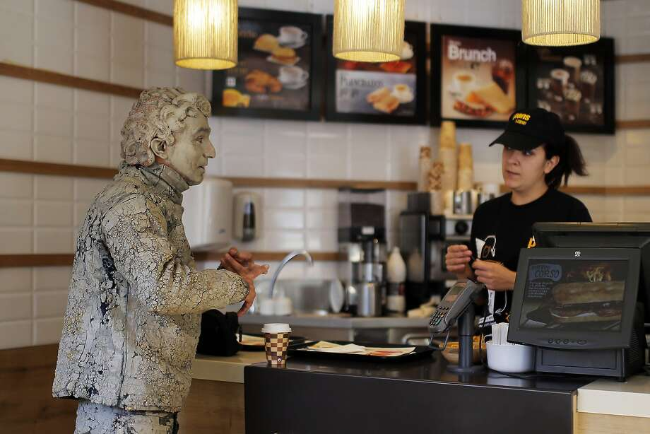 This is me miming paying my bill:A fast-food restaurant worker takes an order from a street performer in 