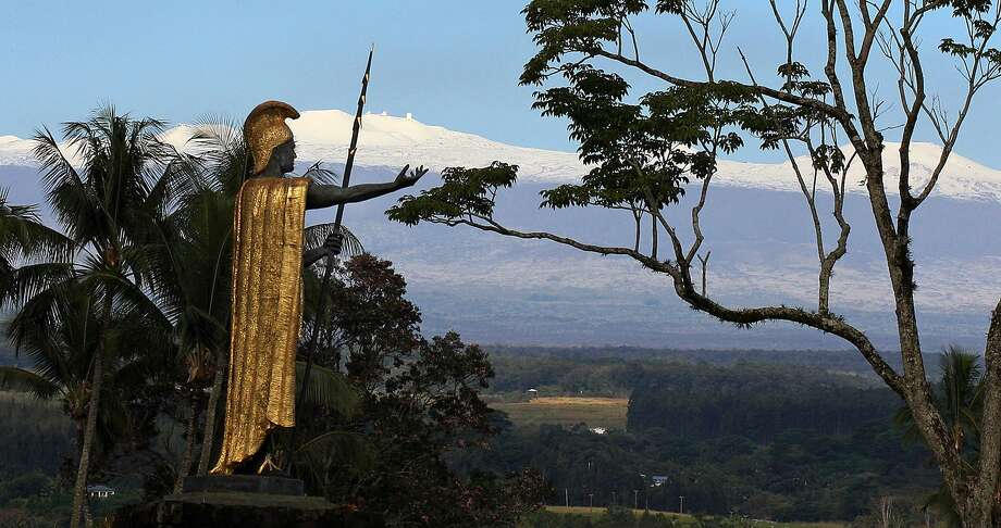 Wax your snowboards, Hawaiians:A fresh blanket of snow covers dormant volcano Mauna Kea behind a statue of Hawaiian King Kamehameha in Hilo. The highest point in Hawaii received 6 to 12 inches at the 10,000-foot   level. Photo: Tim Wright, Associated Press