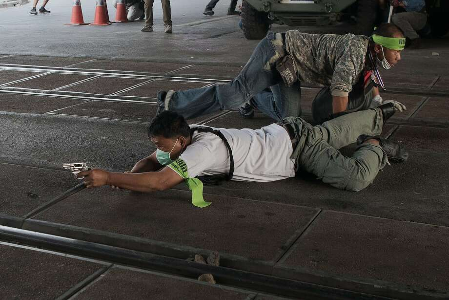 Protest turns into gunfight:A Thai anti-government protester dives to the ground and begins firing at pro-election protesters in   Bangkok. Violence punctuated by explosions and gunfire erupted on the eve of tense Thai elections. Photo: Nicolas Asfouri, AFP/Getty Images