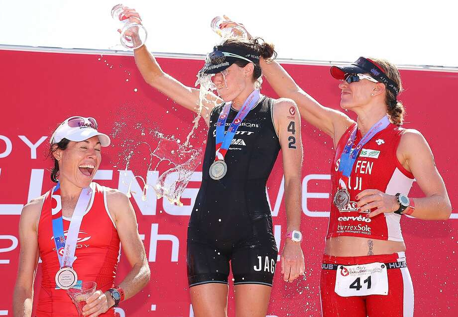 Iron ladies make a splash: Annabel Luxford (center) of Australia celebrates her win with runner-up Caroline Steffen (right) of Switzerland and a refreshing beverage during the Challenge Australia triathlon series in Melbourne. At left is third-place finisher Rebecca Hoschke of Australia. Photo: Michael Dodge, Getty Images