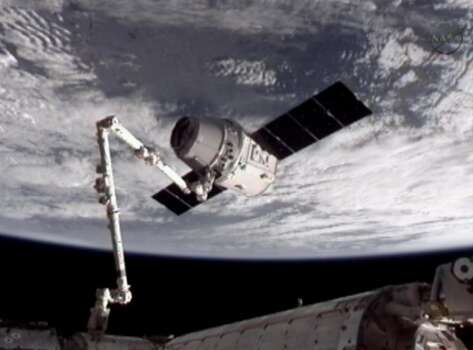 NASA-TV shows the Canadarm 2 robotic arm grip the Dragon for docking to the International Space Station on May 25, 2012.  (NASA / Associated Press) Photo: Associated Press