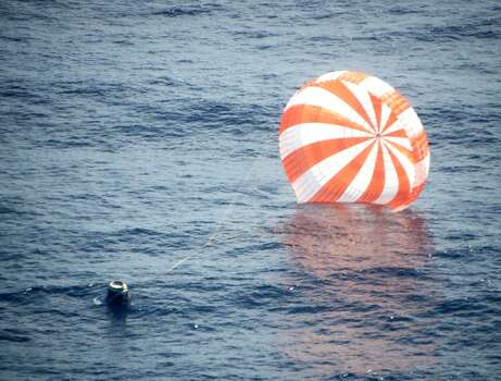 This photo provided by SpaceX shows an unmanned Dragon freighter during its splashdown, after leaving the International Space Station with a stash of precious medical samples and aimed for a Pacific to end the first official shipment under a billion-dollar contract with NASA, Sunday, Oct. 28, 2012. Astronauts aboard the International Space Station used a giant robot arm to release the commercial cargo ship 255 miles up. The California-based SpaceX companysteered  its capsule back to Earth via parachutes on Sunday afternoon, a couple hundred miles off the Baja California coast. (AP Photo/SpaceX) Photo: Associated Press