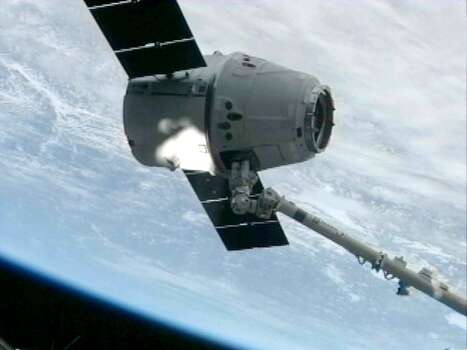 This NASA image form video shows the SpaceX capsule Dragon being captured by the Canada Arm on board the International Space Staion(ISS) on March 3, 2013.  The privately-owned unmanned US space capsule owned by SpaceX arrived at the International Space Station on Sunday, bringing to the space outpost food, scientific materials and other crucial equipment. The capsule named Dragon was captured -- with the help of a robotic arm - by NASA Expedition 34 Commander Kevin Ford and Flight Engineer Tom Marshburn, 5:31 am EST (1031 GMT), when the ISS was over northern Ukraine, US space officials said. (NASA                                   HO/AFP/Getty Images) Photo: HO, AFP/Getty Images