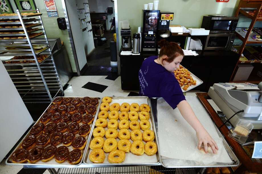 Lauran Wilson consolidates some of the baked goods at Daviss Donuts and Deli on Tuesday morning. The bakery, located in Nederland, is the CAT5 Restaurant of the Week for January 30, 2014. Photo taken Tuesday, 1/21/14 Jake Daniels/@JakeD_in_SETX