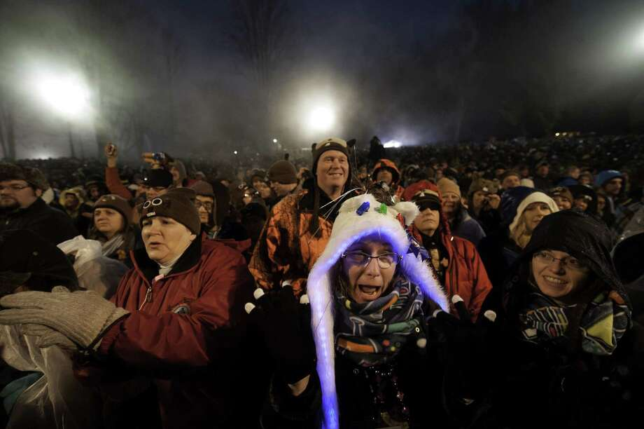 PUNXSUTAWNEY, PA - FEBRUARY 2: Dr Missy Fraser, of Boston, Massachusetts, celebrating her 40th birthday, cheers as Punxsutawney Phil sees his shadow predicting six more weeks of winter during 128th annual Groundhog Day festivities on February 2, 2014 in Punxsutawney, Pennsylvania. Groundhog Day is a popular tradition in the United States and Canada. A smaller than usual crowd this year of less than 25,000 people spent a night of revelry awaiting the sunrise and the groundhog's exit from his winter den. If Punxsutawney Phil sees his shadow he regards it as an omen of six more weeks of bad weather and returns to his den. Early spring arrives if he does not see his shadow, causing Phil to remain above ground. (Photo by Jeff Swensen/Getty Images) ORG XMIT: 463533695 Photo: Jeff Swensen, Getty / 2014 Getty Images