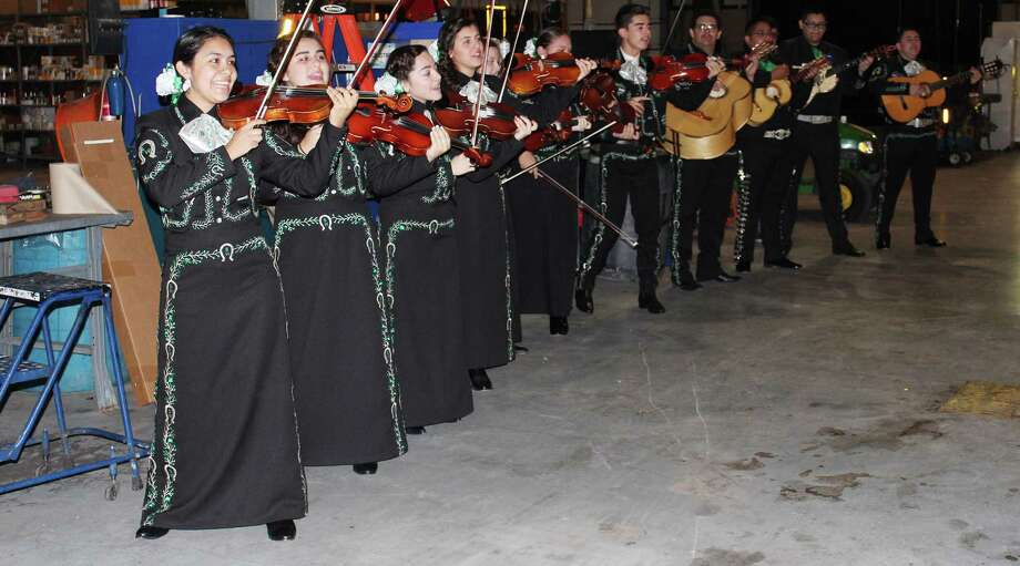 Los Dragones, the Southwest High School mariachi ensemble, showcase their talent and enthusiasm as easily in a garage as on a theater stage. Here, the group provides a serenata for the district's bus drivers at the start of the 2013-14 school year. Los Dragones are in this year's mariachi state finals, set for Saturday. Photo: Courtesy Photo