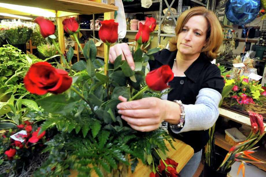 Lauren Ziegler arranges a dozen roses in a vase for Valentine's Day at Judd's Flowers & Plants in Danbury, Friday, Feb. 11, 2011. Photo: Michael Duffy, News Times / The News-Times