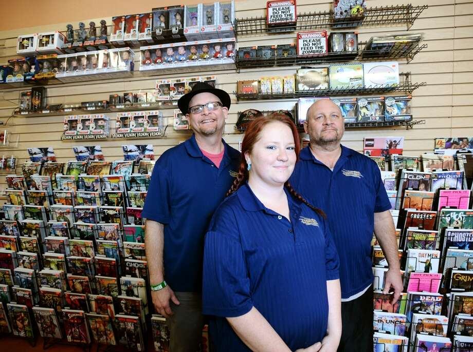 Brothers and Lyons Den co-owners Kelly and Leonard Lyons, back left and right, pose for a picture with daytime manager Dominique Davis, front, on Tuesday afternoon. Lyons Den in Vidor is the CAT5 FreshBiz for Jan. 30, 2014. The shop caters to comic fans and gamers alike, and hosts tournaments and participates in Free Comic Book Day. Photo taken Tuesday, 1/21/14 Jake Daniels/@JakeD_in_SETX