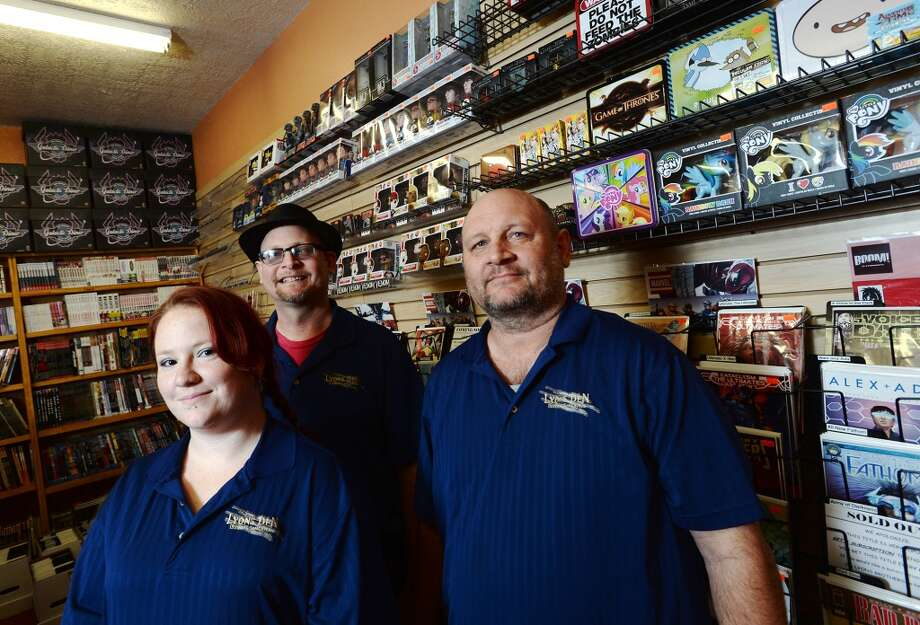 Dominique Davis, daytime manager, left, poses with brothers and Lyons Den co-owners Kelly and Leonard Lyons, center and right, for a picture on Tuesday afternoon. Lyons Den in Vidor is the CAT5 FreshBiz for Jan. 30, 2014. The shop caters to comic fans and gamers alike, and hosts tournaments and participates in Free Comic Book Day. Photo taken Tuesday, 1/21/14 Jake Daniels/@JakeD_in_SETX