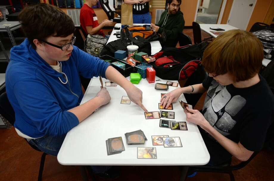 Josh Merrill, left, and Donald Zaicek play Magic: The Gathering at Lyons Den on Tuesday afternoon. Lyons Den in Vidor is the CAT5 FreshBiz for Jan. 30, 2014. The shop caters to comic fans and gamers alike, and hosts tournaments and participates in Free Comic Book Day. Photo taken Tuesday, 1/21/14 Jake Daniels/@JakeD_in_SETX