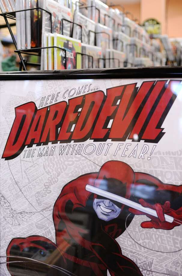 A Daredevil poster leans against a rack of comic books at Lyons Den on Tuesday afternoon. Lyons Den in Vidor is the CAT5 FreshBiz for Jan. 30, 2014. The shop caters to comic fans and gamers alike, and hosts tournaments and participates in Free Comic Book Day. Photo taken Tuesday, 1/21/14 Jake Daniels/@JakeD_in_SETX