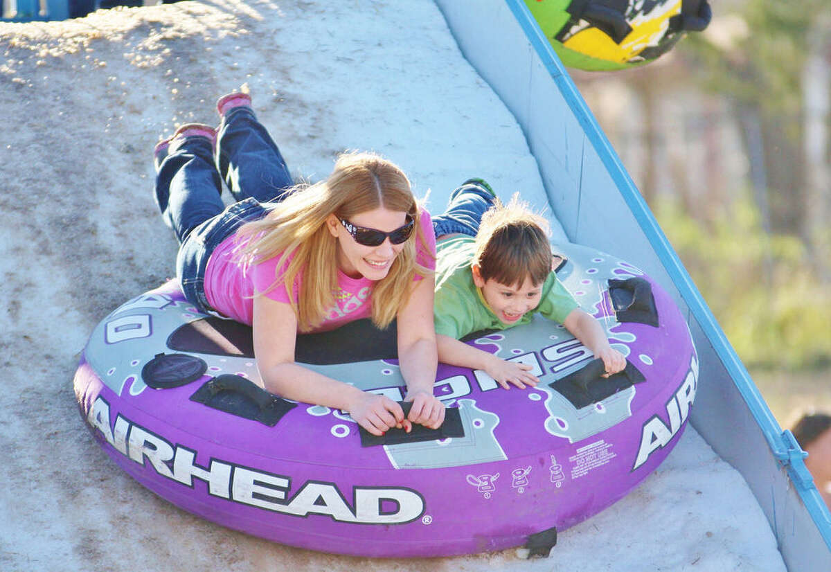 Kayla Rios, left, and her son, Cash Rios, 5, of Maxwell enjoy a trip down the snow ramp during last year's Universal City Snow Fest and Carnival at City Park. The event will be held again Feb. 15.