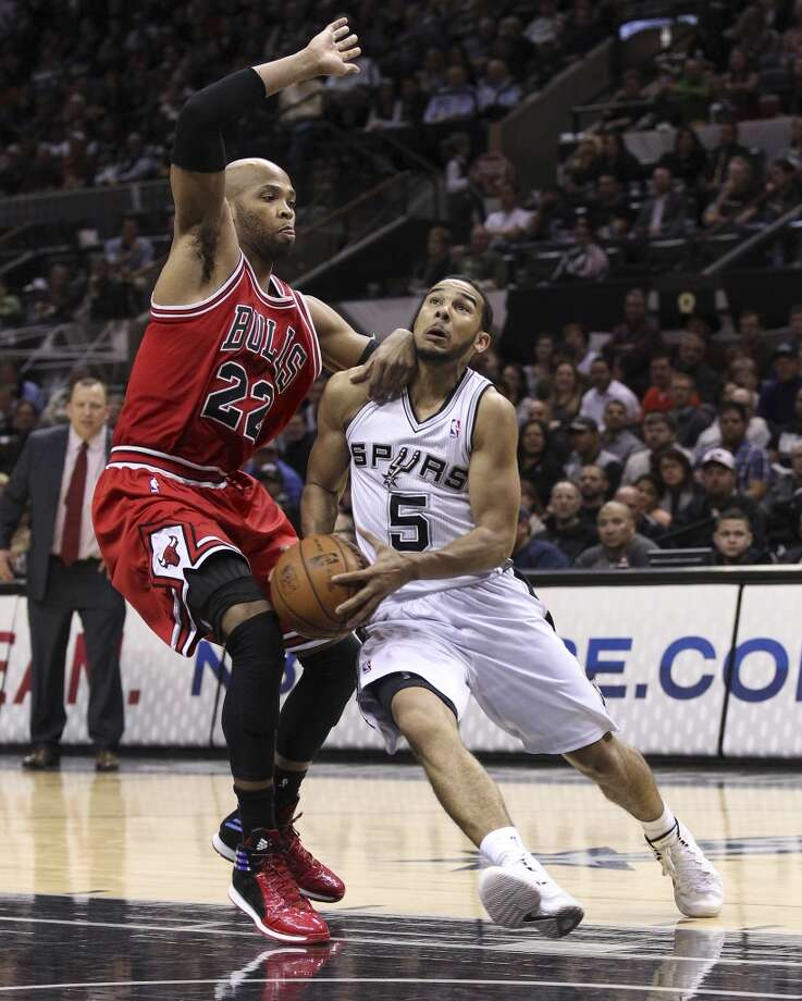 Spurs' Cory Joseph (05) gets defended by Chicago Bulls' Taj Gibson (22) at the AT&T Center on Wednesday, Jan. 29, 2014. Spurs lose the Bulls, 86-96. Photo: Kin Man Hui, San Antonio Express-News